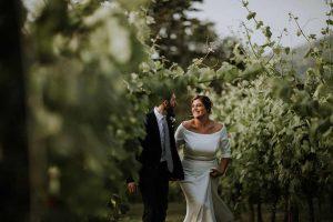 sposi camminano in un vigneto al matrimonio