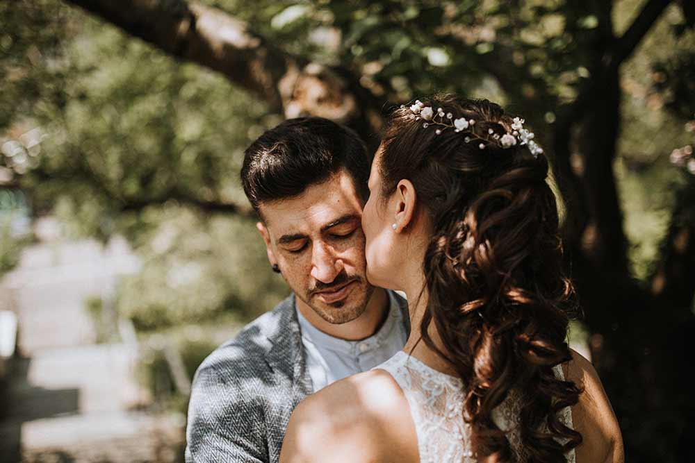sposo e sposa si baciano sotto un'albero