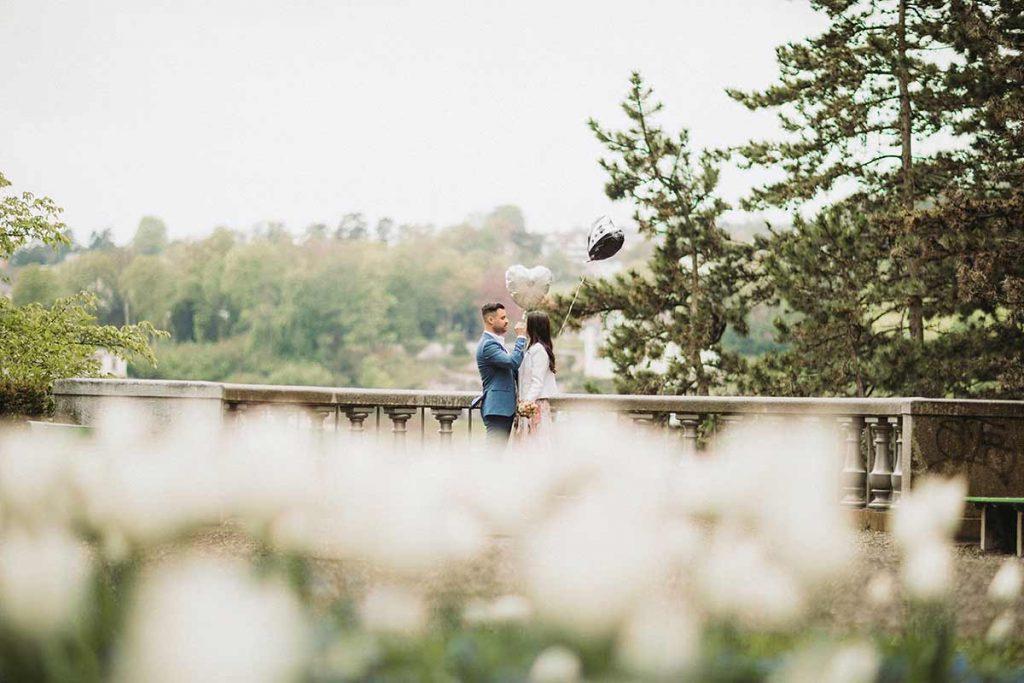 sposo con vestito blu e palloncini per la sposa
